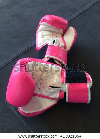 A pair of used pink boxing gloves/mitts on black boxing ring's floor - close up - stock photo