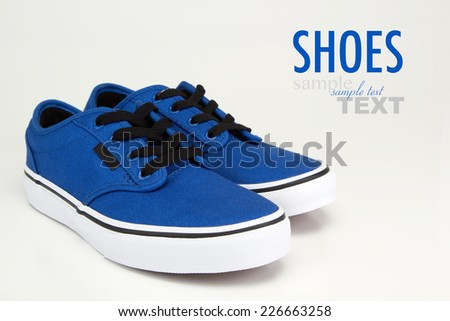 A pair of vintage blue canvas sneakers with black laces. Shoes shot in studio on a white background with sample text. - stock photo