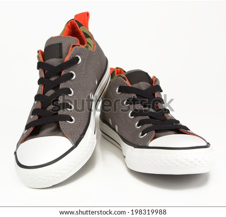 A pair of vintage grey canvas sneakers with camouflage trim and black laces. Shoes shot in studio on a white background.  - stock photo