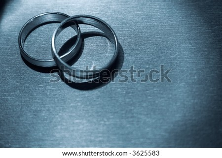 A pair of wedding bands against a textured background.