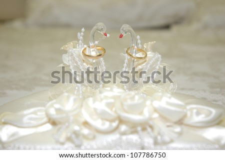 a pair of wedding rings in a swan-shaped container - stock photo
