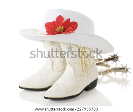 A pair of white cowgirl boots topped by a white hat with a red poinsettia with spurs laying nearby.  On a white background.  - stock photo