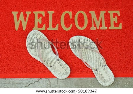 A Pair Of White Slippers On A Welcome Mat - stock photo