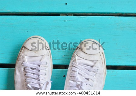 A pair of white sneakers on wooden surface - stock photo