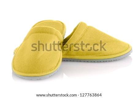 A pair of yellow slippers on a white background. - stock photo