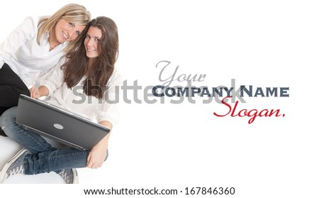 A pair of young laughing female friends using a laptop  - stock photo