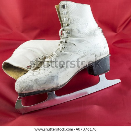 A pair old battered white figure skates with shiny blades on a red background. - stock photo