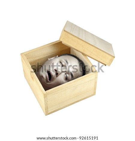 A pale preserved decapitated human head in an open timber box with its lid on the side, isolated against white for Halloween concept. - stock photo