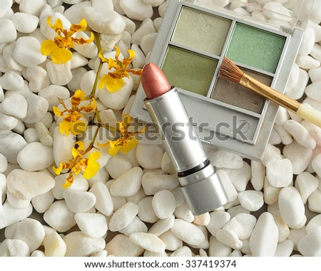 A palette with green shades of eye shadow and a brush, with lip stick displayed on white pebbles with a yellow orchids - stock photo