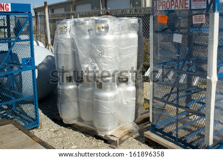 A pallet of new silver propane cylinders at a retail filling center.