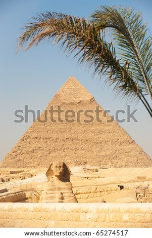 A palm tree frames the classic image of the Great Sphinx and Pyramid of Khafre seen from the entrance of the Giza Pyramids necropolis in Cairo, Egypt - stock photo