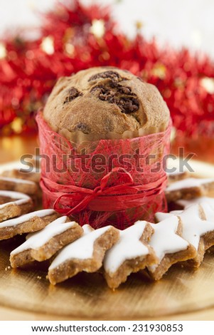 a Panettone on a golden background with red stalks and golden stars