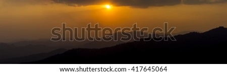 A panorama of a mountain landscape featuring a scene of a setting sun with intertwining mountain ridges, soft focus - stock photo