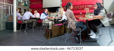 A panorama of a restaurant with eight people enjoying a drink - stock photo