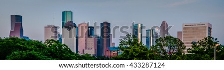 A panorama of a super moon, full moon rising over the city of Houston, TX skyline behind all of the cities skyscrapers.