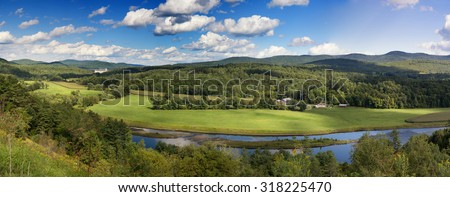 A panorama of the lush green countryside of the State of Vermont in the summertime. A river meanders through the pastures.  - stock photo