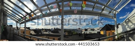A panorama view of clouds and the city from a wide balcony in Helsinki, Finland