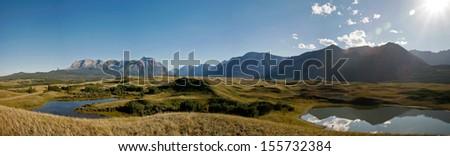 A panorama view of country farm field with mountain background - stock photo