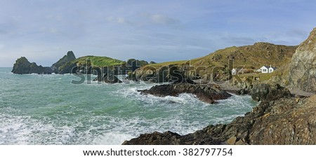A panorama view of Kynance Cove showing the rugged rock formations and nature of the Cove with an incoming tide on a winters day on the Lizard Peninsula Cornwall England UK