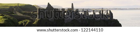 A panorama with details from the famous Dunluce Castle back lit - a landmark from County Antrim, Northern Ireland. - stock photo