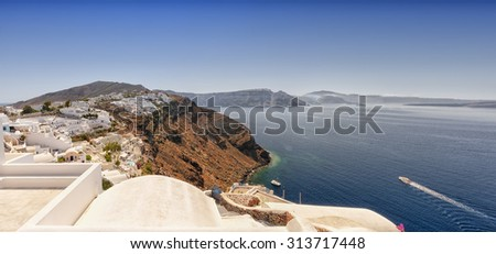 A panoramic image from Santorini of the village of Oia with Imerovili and Fira in the distance. - stock photo