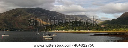 A panoramic image of Loch Leven from the village of Ballachulish near Glencoe, with sailing boats in the water and sunlit mountains in the distance.
