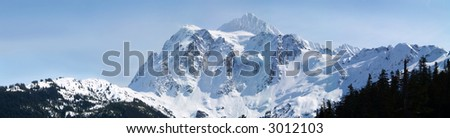 a panoramic shot of a snow covered mountain range in washington with a blue sky on the background.