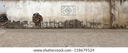 A panoramic stretch of damaged old masonry wall with a patched up hole, along a cobble stone sidewalk. - stock photo