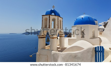 A panoramic view of a couple of the famous blue domed churches from Oia on the greek isle of Santorini.