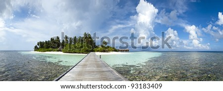 A panoramic view of a paradise island with wood pontoon, blue lagoon and palmtree - stock photo