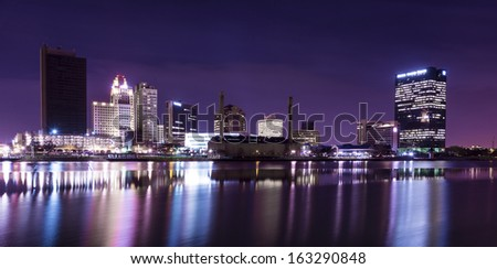 A panoramic view of downtown Toledo Ohio's skyline at night from across the Maumee river.  A beautiful  purple sky with the city lights reflecting into the Maumee river. - stock photo