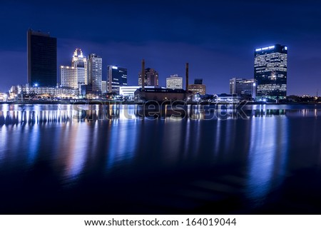 A panoramic view of downtown Toledo Ohio's skyline at night from across the Maumee river.  A beautiful  deep blue sky with the city lights reflecting into the Maumee river. - stock photo