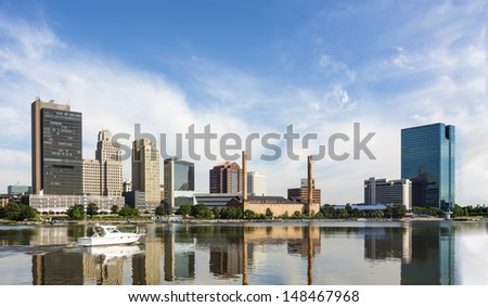 A panoramic view of downtown Toledo Ohio's skyline reflecting into the Maumee river with a power boat cruising by.  A beautiful  blue sky with white clouds for a backdrop. - stock photo