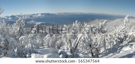 A panoramic view of Lake Tahoe on a very cold sunny winter day after a big snowstorm, shot from one of the mountain tops. Deep snow covers the land, pines and surrounding snowcapped mountains. - stock photo