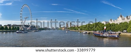 A panoramic view of Thames river in London, England with Houses of Parliamant and London Eye visible - stock photo