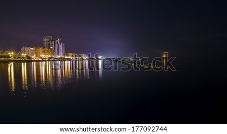 A panoramic view of the cityscape and waterfront of the beautiful city of Limassol in Cyprus. Clear view of the town lights reflected in the calm seawater in the night and the moon rising from the sea - stock photo