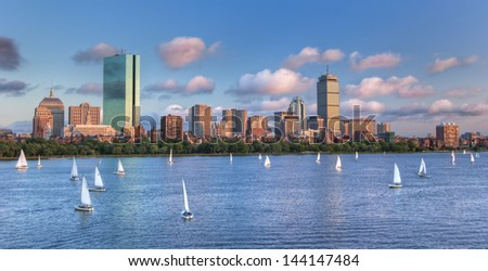 A panoramic view of the full Boston skyline with the Charles River full of sailboats as sunset approaches - stock photo