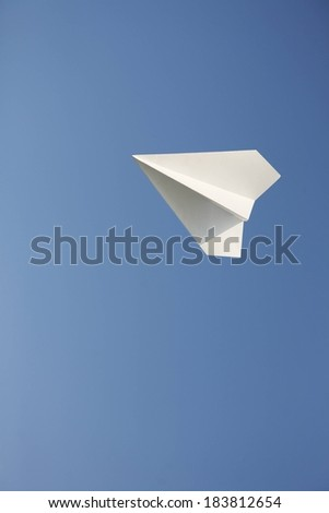 A paper airplane flying high in the sky. - stock photo