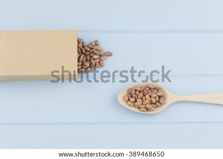 A paper bag, some speckled beans and a spoon on a blue wooden table - stock photo