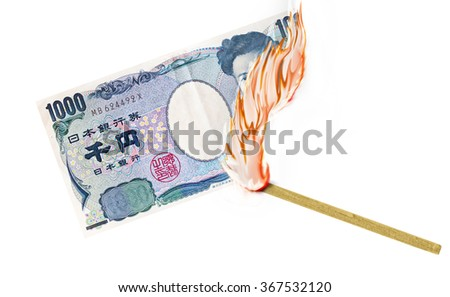A paper bill being burned by a lid match. - stock photo