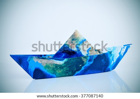 a paper boat made with a world map (furnished by NASA), with a slight vignette added - stock photo