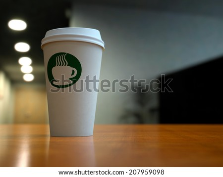 A paper coffee cup in an office or coffee shop setting with a green coffee logo - stock photo