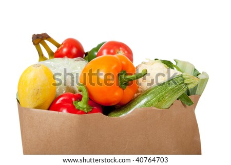 A paper grocery sack with vegetables including peppers, asparagus, celery, tomatoes, squash and broccoli on a white background - stock photo