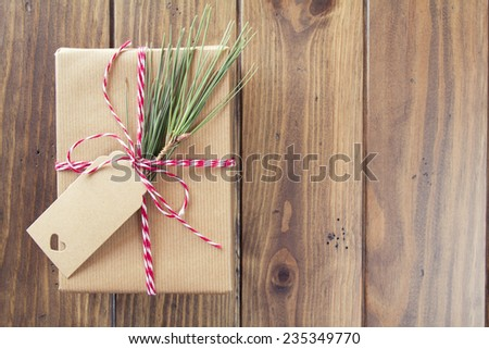 A paper parcel wrapped tied with a tag. A christmas gift box wrapped with paper kraft and tied with red & white baker's twine on a wooden table. Vintage Style. - stock photo