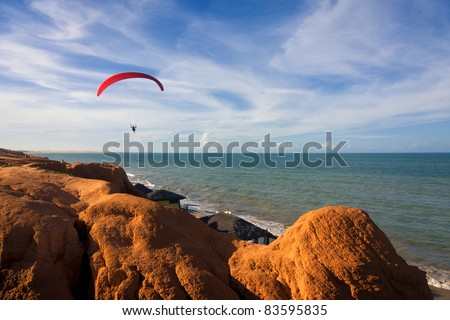 A para-glide soars over a tropical beach backed by red hills - stock photo