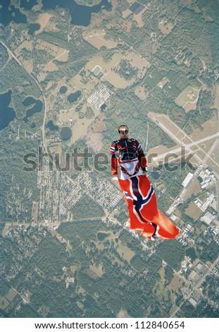A parachute jumper holding a Norwegian flag, USA. - stock photo