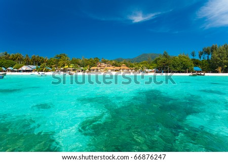 A paradise with perfect crystal clear turquoise ocean water, coral reef and holiday resorts on pure white sand beach on Ko Lipe island, Thailand. Horizontal