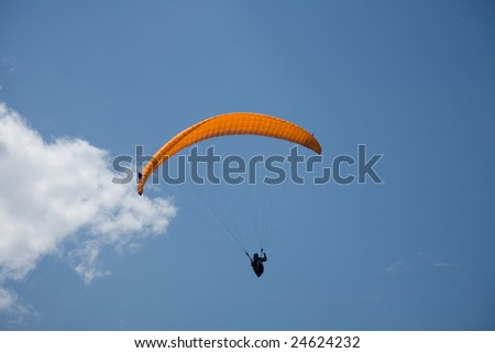 A Paraglider flies in the blue sky.