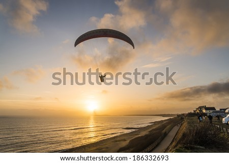 A paraglider flying over a beach in Bournemouth,Dorset,UK.