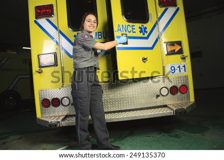 A paramedic, on the back door of the ambulance - stock photo